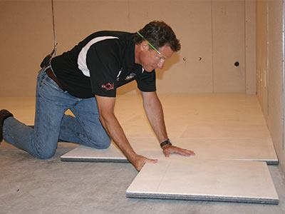 Contractor installing the ThermalDry® insulated subfloor system in a basement